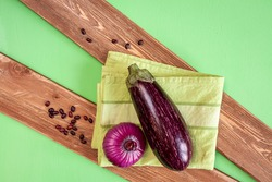 an aubergine, onion, haricot beans and green towel on brown wood boards on green background