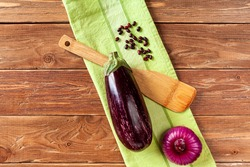 an aubergine, onion, wooden cooking spatula and haricot beans on green towel on brown wooden background