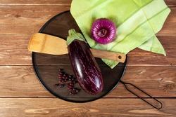 an aubergine, onion, wooden cooking spatula, haricot beans, black cover and green towel on brown wooden background