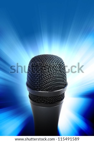 An audio microphone is glowing on a blue background. Use it for a music or entertainment concept.