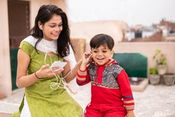 An aunt listening music and sharing headphones with her cute little nephew. They are sitting together and enjoying their leisure time. She is wearing traditional Indian dress salwar Kameez and Dupatta