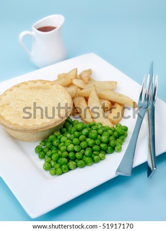 An Australian meat pie served with peas and chips isolated against a blue background - stock photo