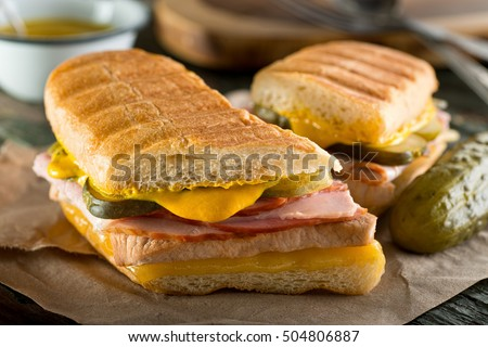 Shutterstock An authentic cuban sandwich on pressed medianoche bread with pork, ham, cheese, pickle, and mustard.