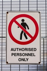 An authorised personnel only safety sign on a mesh metal gate on a stairwell