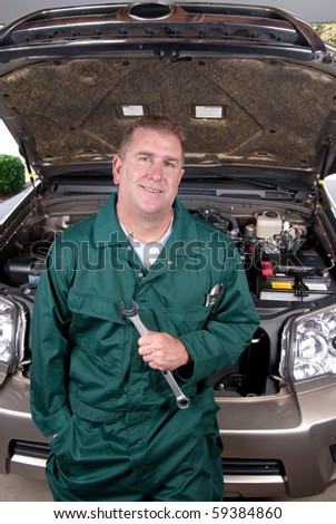 An auto mechanic holds a wrench before conducting engine repair and maintenance on a car.
