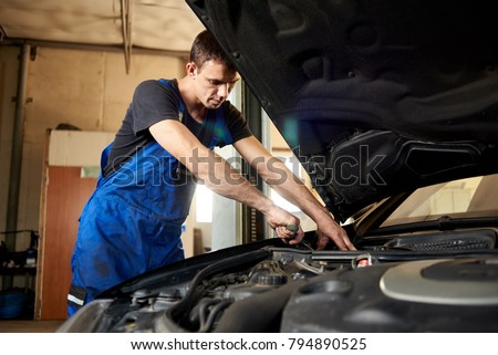 An auto mechanic in a dirty work uniform repairs a car in the garage. The bonnet is open, the guy looks carefully at the problem #794890525