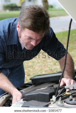 An auto mechanic looking under the hood of a car. Vertical view.