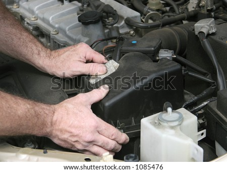 An auto mechanic removing the cover from a car air filter.