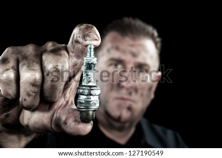 An auto mechanic shows a damaged and worn spark plug as he performs a tune up.
