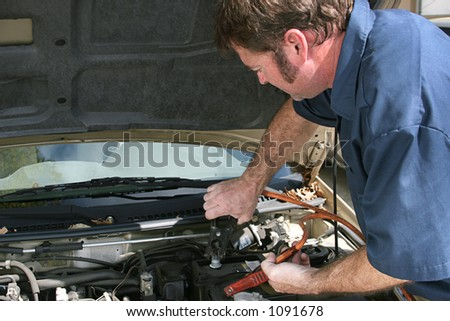 An auto mechanic using jumper cables on a car battery.  Horizontal with copy space for text.