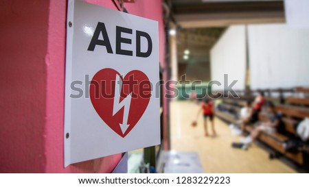 An automated external defibrillator symbol in front of the gymnasium. The AED using in emergency situation such as acute cardiac arrest. The basketball players was playing in blurred background. #1283229223
