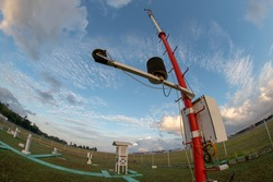 An Automatic Weather Station at Bali Meteorology Station with a landscape of Meteorological garden in the morning. Under the blue sky with partly grey cumulus and cirrus clouds. Shoot on fisheye lens