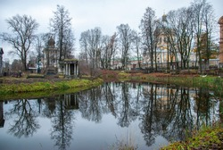 An autumn view on the Monastery Island with churches, trees and an old cemetery reflecting in the pond, Saint Petersburg, Russia