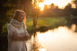 An autumnal portrait of a young, lost in thought woman looking at pond in the park on sunset