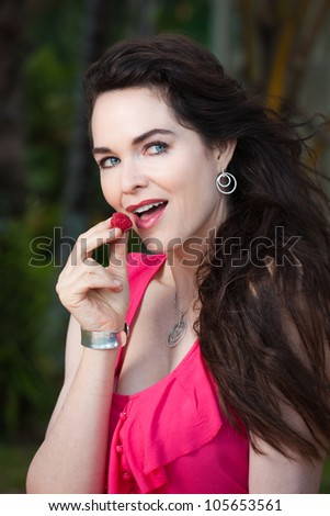 An beautiful young lady eating raspberries - stock photo