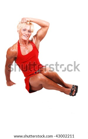 An blond bodybuilding girl sitting in a studio in a red dress and shooing her very muscular body with high heels, over white  background.