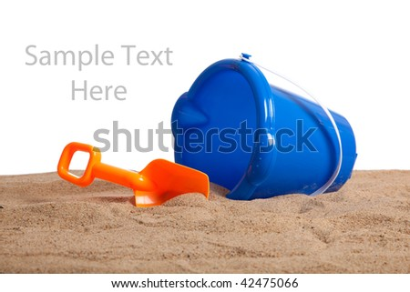 An blue bucket and orange shovel on a sandy beach with copy space on a white background