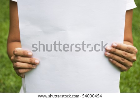 an board/paper that hold by a girl, with grass field background.