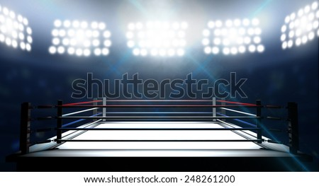 An boxing ring surrounded by ropes spotlit by floodlights in an arena setting at night Foto stock ©