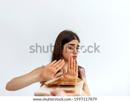 An Caucasian young woman feels bad, has an upset stomach, bloating due to gluten intolerance. Gluten products intolerant people. The concept of a healthy lifestyle and intolerance for gluten products. Zdjęcia stock ©