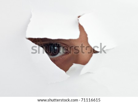 An  child\'s eye looking through a hole in a  white sheet of paper