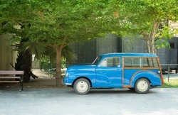 An classic blue car awaiting renovation ,blue car renovation at boutique resort, retro resident,vehicle is parked, Small car. bule color