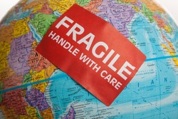 An Earth globe with a fragile hand with care sticker