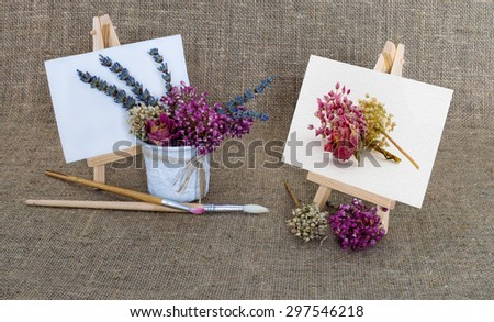 an easel, paints and a bouquet of dried flowers