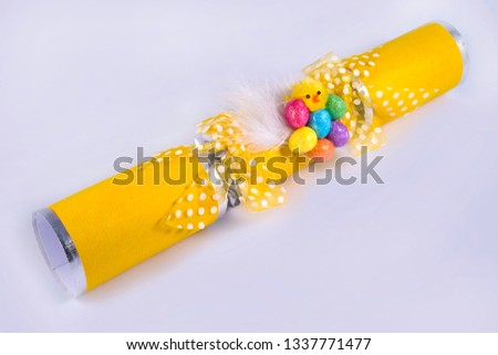 An Easter Cracker or otherwise known as a Bon Bon. A traditional cracker consists of a cardboard tube wrapped in a brightly decorated twist of paper with a gift in the central chamber