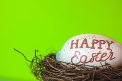 An Easter egg with a calligraphic inscription Happy Easter in a bird's nest on a bright green natural Easter background. Spring religious holiday. Banner with space for greeting text.