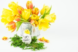 An Easter egg with a chick and the words Happy Easter, behind yellow tulips, white background
