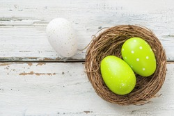 An easter nest with green easter eggs on a wooden background