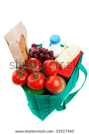 An eco-friendly, reusable, green cloth bag full of groceries.  Shot on white background.
