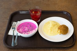 an economical, not expensive lunch with mashed potatoes, cold beetroot soup and turkey cutlet on a plastic tray in a diner