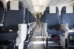 An economy class empty clean cabin of the airplane - empty dark blue chairs