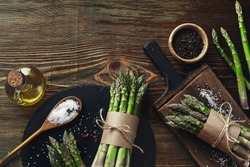 An edible, raw stems of asparagus on a wooden background.