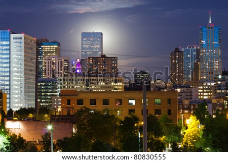 An eerie glowing moon rises  behind a tall skyscraper in the Denver Colorado skyline.