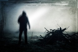 An eerie silhouette of a lone hooded figure in a field With a dark, spooky blurred abstract, grunge effect edit.