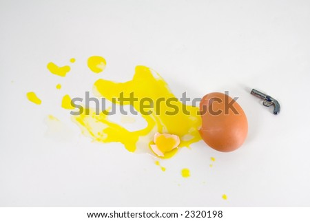 An egg commits suicide by putting a gun to its head - stock photo