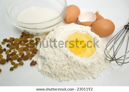 An egg in a pile of flour preparing for baking with kitchen tools sugar and raisins