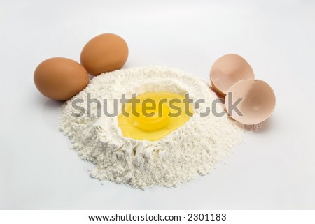An egg in some flour preparing for baking with eggs and egg shells in the sides