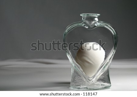 An egg inside a heart shaped vase, possibly symbolizing love and fertility.