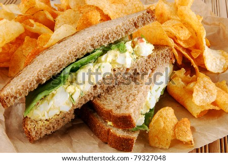 An egg salad sandwich with barbecued potato chips on brown paper