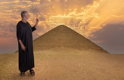 An Egyptian in black robe stands in front of the pyramid of Darzhur in Lower Egypt. He points to the monument with one finger. The sun is setting behind the pyramid.