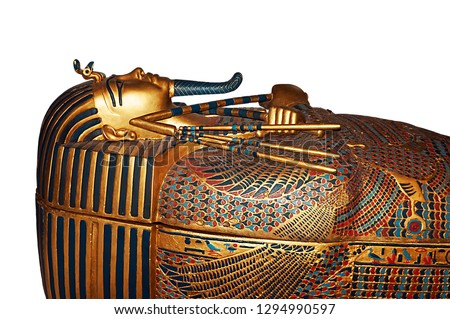 An egyptian mummy sarcophagus made of gold with carved details. The image has been isolated on white background.