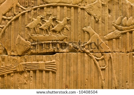 An Egyptian rock carving of a cat about to attack a bird nest