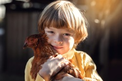 An eight-year-old boy with blond hair gently hugs a brown hen.