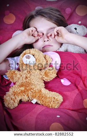 an eight-year-old girl in bed with blanket and pillows and stuffed animals