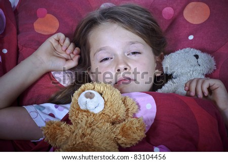 an eight-year-old girl in bed with blanket and pillows and stuffed animals - stock photo