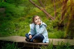 An eight-year-old girl observes natural phenomena under the sun in the forest. A child sits on a bridge with legs crossed.